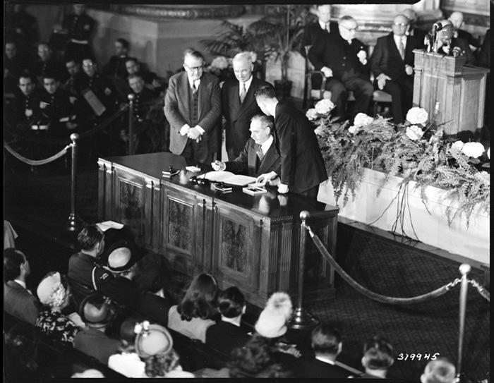 Dean Acheson (Ministro degli Esteri statunitense)firma il trattato NATO.